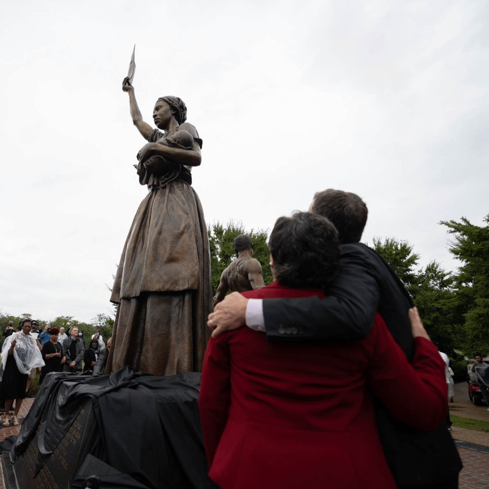 Two people standing next to the Emancipation and Freedom Monument in Richmond, VA with arms around each other