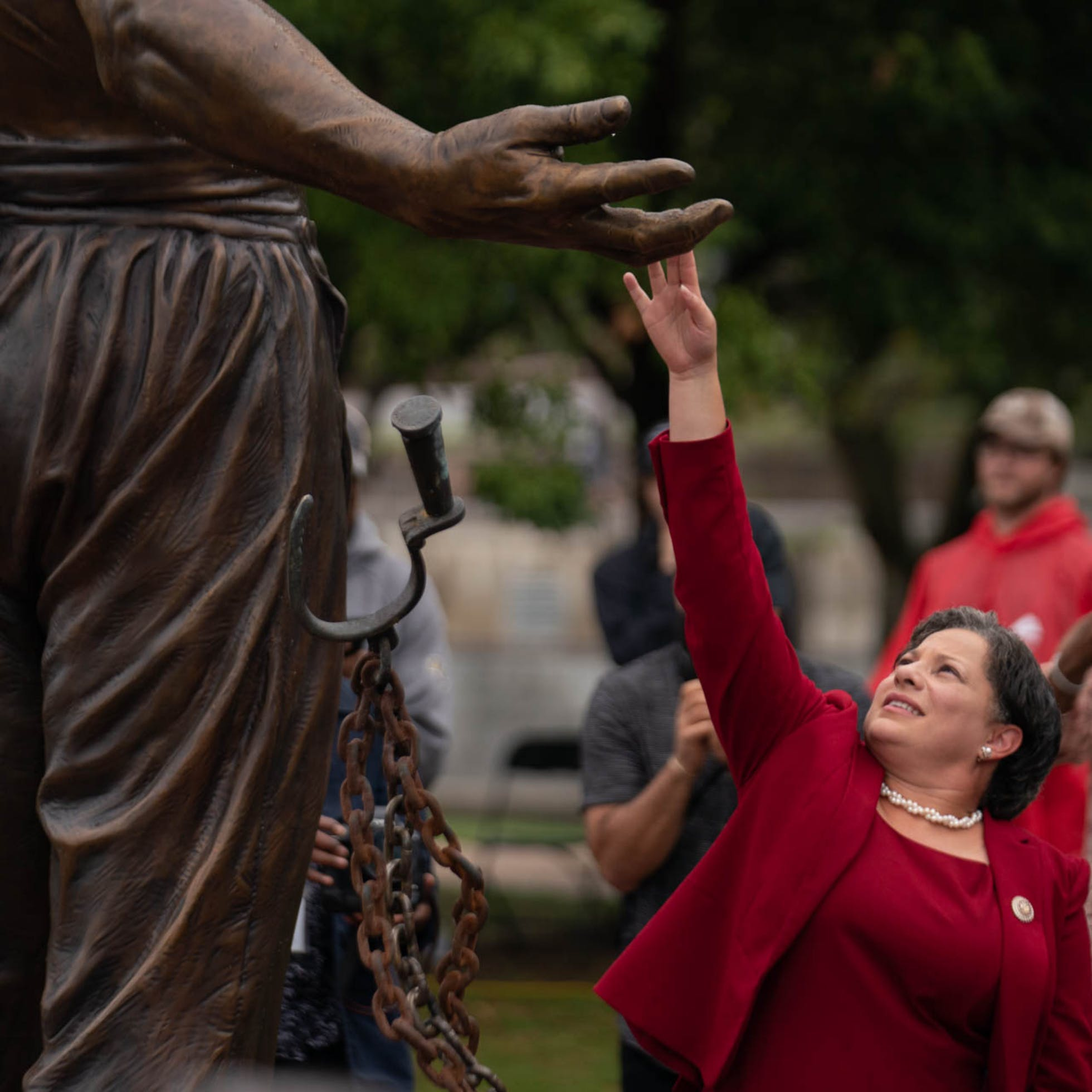 A woman touching the hand of the freed male slave statue depicted in the Emancipation and Freedom Monument in Richmond, VA